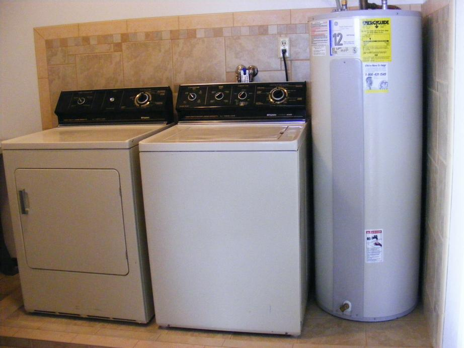 Front View of Utility Room Ceramic Tile Wall with Washer, Dryer and Water Heater Installed